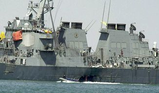 In this Oct. 15, 2000, file photo, experts in a speed boat examine the damaged hull of the USS Cole at the Yemeni port of Aden after an al Qaeda attack that killed 17 sailors. The Supreme Court on Tuesday threw out a nearly $315 million judgment against Sudan stemming from the USS Cole bombing, saying Sudan hadn't properly been notified of the lawsuit. (AP Photo/Dimitri Messinis, File)