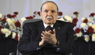 FILE - In this April 28, 2014 file photo, Algerian President Abdelaziz Bouteflika, sitting in a wheelchair, applauds after taking the oath as President in Algiers. Algeria's powerful army chief wants to trigger the constitutional process that would declare ailing President Abdelaziz Bouteflika unfit for office. (AP Photo/Sidali Djarboub, File)