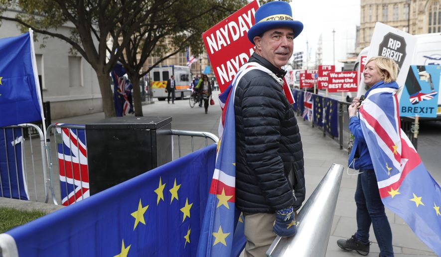 Steve Bray, an anti Brexit protester, holds onto a large megaphone as he demonstrates outside the House of Parliament in London, Tuesday, March 26, 2019. British Prime Minister Theresa May's government says Parliament's decision to take control of the stalled process of leaving the European Union underscores the need for lawmakers to approve her twice-defeated deal. (AP Photo/Alastair Grant)