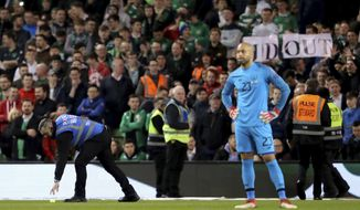 Tennis balls are thrown on to the pitch to interrupt game time in protest of Chief Executive of the Football Association of Ireland John Delaney during the UEFA Euro 2020 Qualifying, Group D match at the Aviva Stadium, Dublin. (Niall Carson/PA via AP)