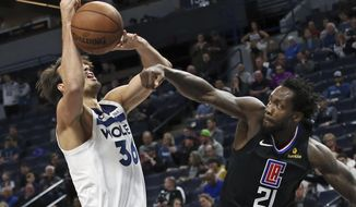 Los Angeles Clippers' Patrick Beverley, right, knocks the ball away from Minnesota Timberwolves' Dario Saric in the first half of an NBA basketball game Tuesday, March 26, 2019, in Minneapolis. (AP Photo/Jim Mone)