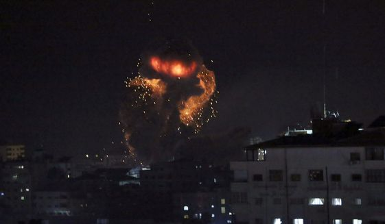 An explosion caused by Israeli airstrikes is seen from the offices of Hamas leader Ismail Haniyeh, in Gaza City, Monday, March 25, 2019. Israeli forces on Monday struck targets across the Gaza Strip in response to a surprise rocket attack from the Palestinian territory, as the military beefed up troops and rocket-defense systems in anticipation of a new round of heavy fighting with the Islamic militant Hamas group. (AP Photo/Adel Hana)