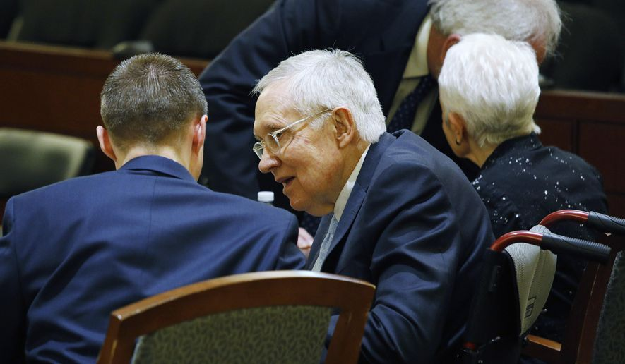 Former U.S. Sen. Harry Reid, second from left, sits in court Tuesday, March 26, 2019, in Las Vegas. A jury in Nevada heard opening arguments Tuesday in Reid's lawsuit against the maker of a flexible exercise band that he says slipped from his hand while he used it in January 2015, causing him to fall and suffer lasting injuries including blindness in one eye. (AP Photo/John Locher)