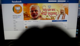 A woman checks the Facebook page of India's ruling Bharatiya Janata Party, in New Delhi, India, Tuesday, March 26, 2019.  Facebook says it is preparing for Indian elections by working to limit false stories, videos and photos on its platform. Indian politicians increasingly are using social media to run campaign advertisements, share political songs and interact with young voters. Polling in the general election is to take place in seven stages from April 11 to May 19. (AP Photo/Manish Swarup)