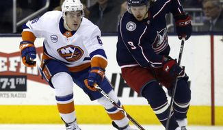 Columbus Blue Jackets forward Artemi Panarin, right, of Russia, chases the puck against New York Islanders defenseman Ryan Pulock during the first period of an NHL hockey game in Columbus, Ohio, Tuesday, March 26, 2019. (AP Photo/Paul Vernon)