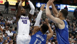 Sacramento Kings forward Harrison Barnes (40) goes up for a shot as Dallas Mavericks' Jalen Brunson (13) and Dwight Powell, right, defend in the first half of an NBA basketball game in Dallas, Tuesday, March 26, 2019. (AP Photo/Tony Gutierrez)