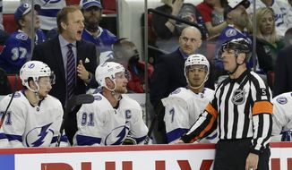 Tampa Bay Lightning coach Jon Cooper, upper left, speaks with an official, front right, during the second period of an NHL hockey game against the Carolina Hurricanes in Raleigh, N.C., Thursday, March 21, 2019. (AP Photo/Gerry Broome)