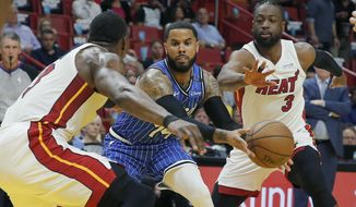 Orlando Magic guard D.J. Augustin, center, passes between Miami Heat center Bam Adebayo, left, and Dwyane Wade, right, in the first quarter during an NBA basketball game Tuesday, March 26, 2019, in Miami.(AP Photo/Joe Skipper)