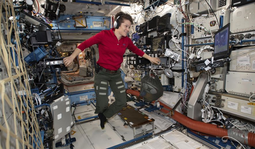In this Jan. 18, 2019, file photo made available by NASA, Flight Engineer Anne McClain looks at a laptop computer screen inside the U.S. Destiny laboratory module of the International Space Station. McClain was supposed to participate in a spacewalk Friday, March 29, 2019, with newly arrived Christina Koch. But McClain pulled herself from the lineup because there's not enough time to get two mediums suits ready. Koch will go out with a male crewmate. (NASA via AP)