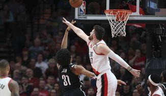 Brooklyn Nets center Jarrett Allen shoots next to Portland Trail Blazers center Jusuf Nurkic during the first half of an NBA basketball game in Portland, Ore., Monday, March 25, 2019. (AP Photo/Randy L. Rasmussen)
