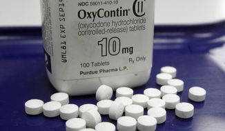 This Feb. 19, 2013, file photo shows OxyContin pills arranged for a photo at a pharmacy in Montpelier, Vt. Oklahoma's attorney general will announce a settlement Tuesday, March 26, 2019, with Purdue Pharma, one of the drug manufacturers named in a state lawsuit that accuses them of fueling the opioid epidemic. (AP Photo/Toby Talbot, File)