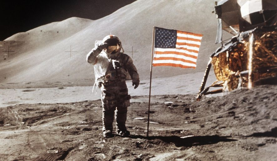 FILE - In this July 30, 1971 photo made available by NASA, Apollo 15 Lunar Module Pilot James B. Irwin salutes while standing beside the fourth American flag planted on the surface of the moon. On Tuesday, March 26, 2019, Vice President Mike Pence called for landing astronauts on the moon within five years. (NASA via AP)