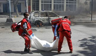 Medics carry away the body of a civilian who was killed when an explosive device planted in his car detonated, in Mogadishu, Somalia Tuesday, March 26, 2019. A Somali police officer says the bomb exploded killing the driver and injuring a nearby pedestrian in the Hodan district of the capital. (AP Photo/Farah Abdi Warsameh)
