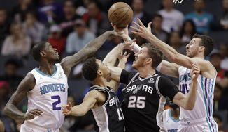 Charlotte Hornets' Marvin Williams (2) and Frank Kaminsky (44) battle San Antonio Spurs' Jakob Poeltl (25) and Bryn Forbes (11) for a rebound during the first half of an NBA basketball game in Charlotte, N.C., Tuesday, March 26, 2019. (AP Photo/Chuck Burton)