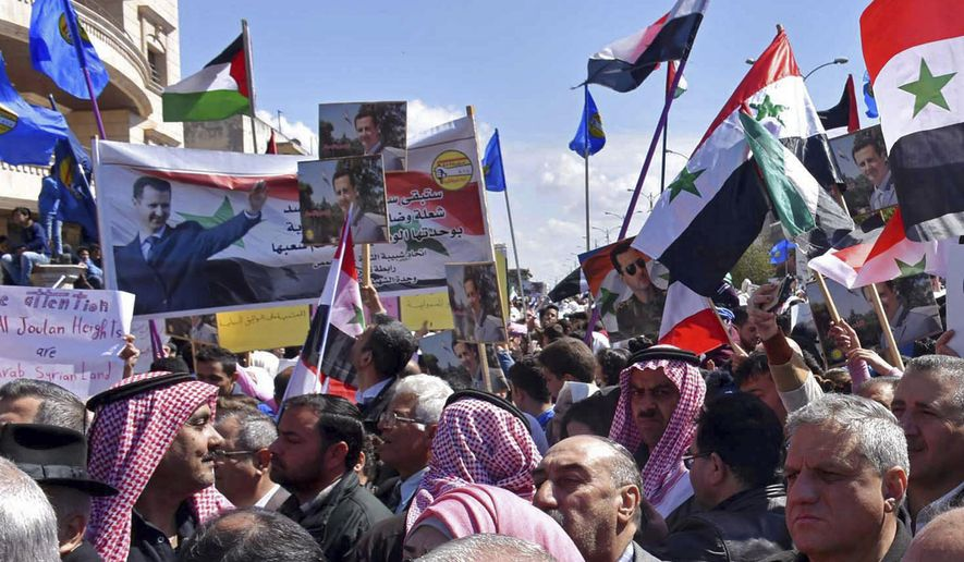 In this photo released by the Syrian official news agency SANA, Syrians hold national flags and portraits of Syrian President President Bashar Assad during a protest against President Donald Trump's move to recognize Israeli sovereignty over the occupied Golan Heights, in Homs, Syria, Tuesday, March 26, 2019. Syria's state news agency says thousands of Syrians have held gatherings in the streets of different cities to protest Trump's signing of a declaration reversing US policy on the Golan Heights. (SANA via AP)