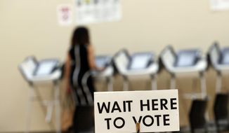 FILE - In this May 9, 2018, file photo, a woman votes in Sandy Springs, Ga. With the presidential primaries less than a year away, security experts and elected officials have expressed concern about whether the state and federal governments have done enough since 2016 to fend off another attack by Russia or other foreign actors. (AP Photo/John Bazemore, File)