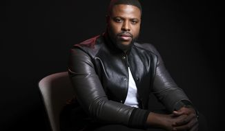 """This March 12, 2019 photo shows Winston Duke, a cast member in the film """"Us,"""" posing at the The London West Hollywood in West Hollywood, Calif. (Photo by Chris Pizzello/Invision/AP)"""
