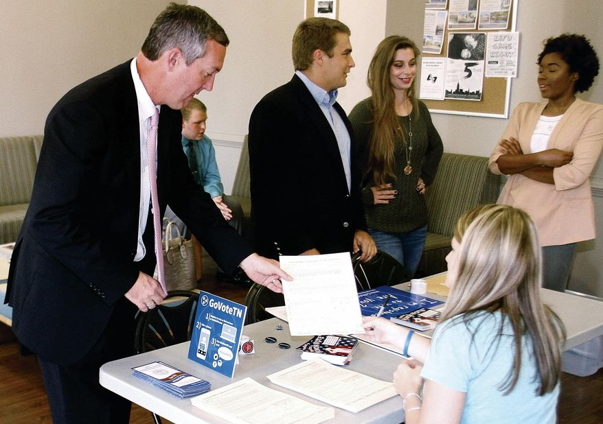 FILE - In this Sept. 29, 2016, file photo, Tennessee Secretary of State Tre Hargett helps Ami Burchfield with voter registration paperwork at Maryville College helping students register to vote, in Maryville, Tenn. Amid growing national concerns about election security, Tennessee's three largest counties are moving toward voting machines that produce a voter-verifiable paper trail for the presidential primaries in 2020. Hargett says he's letting counties decide whether to switch. (The Daily Times via AP, File)