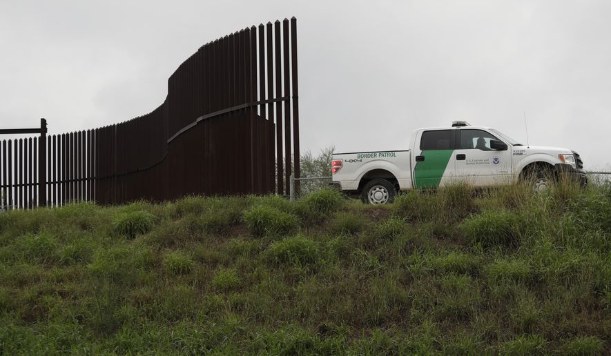 This Nov. 13, 2016, file photo shows a U.S. Customs and Border Patrol agent passing along a section of border wall in Hidalgo, Texas. President Donald Trump will face many obstacles in building his big, beautiful wall on the U.S.-Mexico border, including how to pay for it and how to contend with unfavorable geography and the legal battles ahead. (AP Photo/Eric Gay, File)