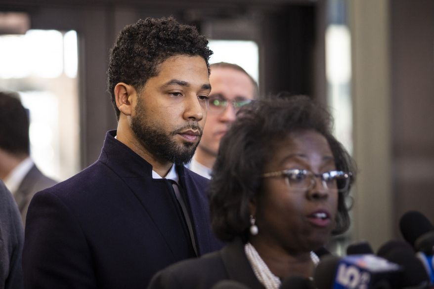 Actor Jussie Smollett, right, listens as his attorney, Patricia Brown Holmes, speaks to reporters at the Leighton Criminal Courthouse after prosecutors dropped all charges against him on Tuesday, March 26, 2019. (Ashlee Rezin/Sun-Times/Chicago Sun-Times via AP)