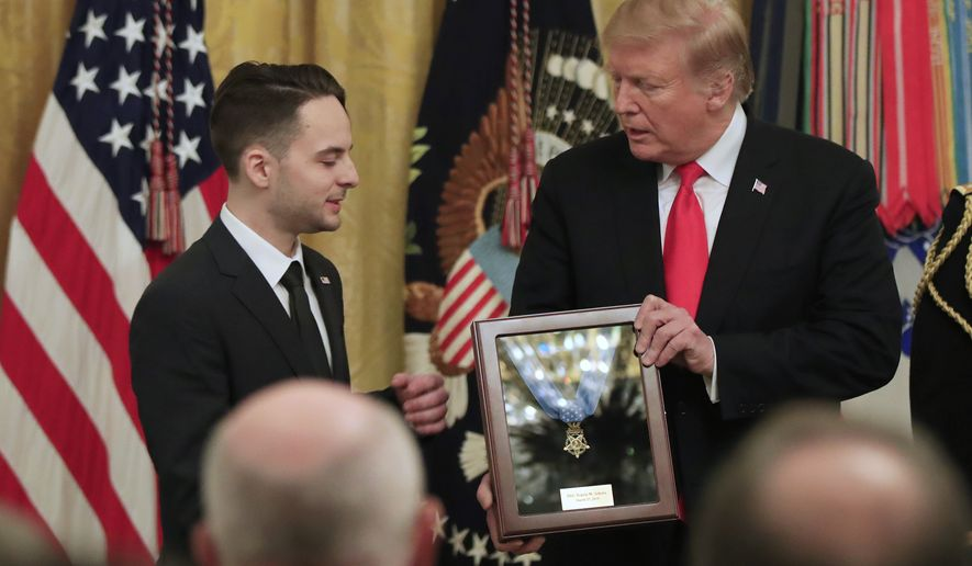 Trevor Oliver accepts the Medal of Honor from President Donald Trump, presented to his father, Army Staff Sgt. Travis Atkins in recognition for conspicuous gallantry in Iraq in June 2007, during a ceremony in the East Room of the White House, Wednesday March 27, 2019, in Washington.(AP Photo/Manuel Balce Ceneta)