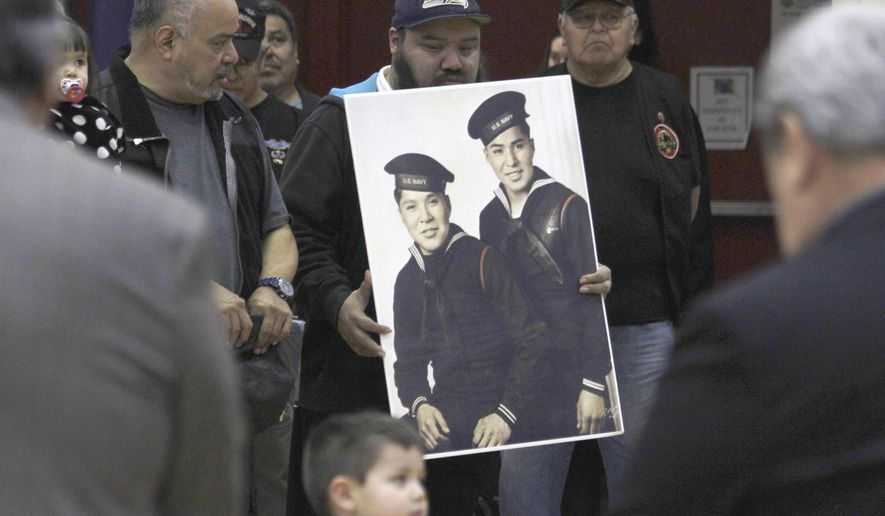 In this Monday, March 18, 2019 photo, family members of brothers Mark Jacobs Jr. and Harvey Jacobs observe a moment of silence during a ceremony honoring Tlingit code talkers in Juneau, Alaska. Five long-deceased Alaska Native servicemen are being hailed by the state of Alaska for their life-saving efforts during World War II. Alaska lawmakers this month passed a formal citation honoring the Tlingit men for using their Native language to help the military outsmart the Japanese with codes they could not break. (Alex McCarthy/The Juneau Empire via AP)