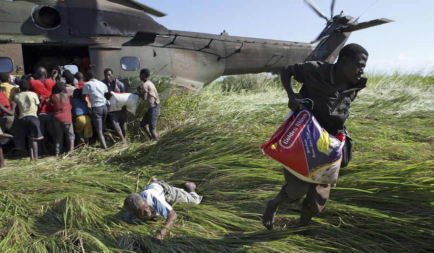 In this Tuesday, March 26, 2019, photo,  an elderly man lies on the ground after his bag of food was snatched from him in a scramble for bags of rice delivered by the South African Airforce helicopter at Nyamatande Village, Mozambique, following the devastating Tropical Cyclone Idai. A second week has begun with efforts to find and help some tens of thousands of people in devastated parts of southern Africa, with some hundreds dead and an unknown number of people still missing. (AP Photo/Phill Magakoe)