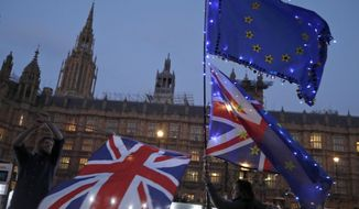 A protestor waves flags outside of the Houses of Parliament in London, Wednesday, March 27, 2019. British lawmakers were preparing to vote Wednesday on alternatives for leaving the European Union as they seek to end an impasse following the overwhelming defeat of the Brexit deal negotiated by Prime Minister Theresa May. (AP Photo/Frank Augstein)