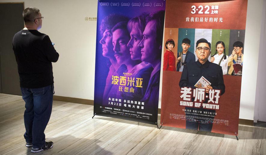 """A customer looks at a movie poster for the film """"Bohemian Rhapsody"""" at a movie theater in Beijing, Wednesday, March 27, 2019. Moviegoers in China say the version of the """"Bohemian Rhapsody"""" shown in Chinese theaters erases mentions of Freddie Mercury's sexuality. The biopic on the lead singer of the British rock band Queen omitted a same-sex kiss and lacked scenes in which Mercury reveals he's not straight and has AIDS. (AP Photo/Mark Schiefelbein)"""