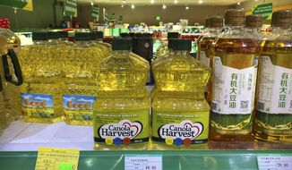FILE - In this March 6, 2019, file photo, bottles of Canola Harvest brand canola oil, manufactured by Canadian agribusiness firm Richardson International, are seen on a shelf of a grocery store in Beijing. China said Wednesday, March 27, 2019 its suspension of the license of a second major Canadian canola exporter is justified by safety concerns, as the sides continue to feud over Ottawa's detention of a top executive of Chinese telecom giant Huawei. (AP Photo/Mark Schiefelbein, File)