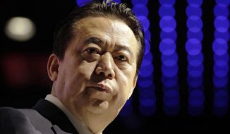 FILE - In this July 4, 2017, file photo, Interpol President Meng Hongwei delivers his opening address at the Interpol World Congress, in Singapore. China has expelled former Interpol chief Meng from public office and the ruling Communist Party. (AP Photo/Wong Maye-E, File)
