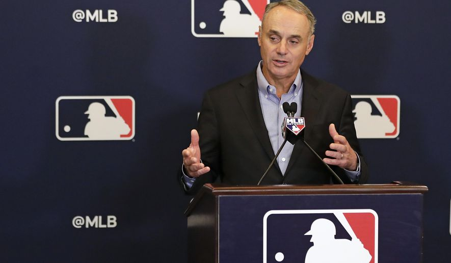 FILE - In this Feb. 8, 2019 file photo, Rob Manfred, commissioner of Major League Baseball, speaks during a news conference at owners meetings in Orlando, Fla. Major League Baseball and Reds are this season commemorating the 150th anniversary of the Cincinnati Red Stockings, who pioneered professional baseball.  Manfred will be grand marshal Thursday, March 28 of the 100th Findlay Market Opening Day Parade in Cincinnati. The colorful parade featuring floats, marching bands and celebrities will begin winding through the city.  (AP Photo/John Raoux, File)