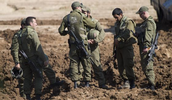 Israeli soldiers work near their tanks at a gathering area near the Israel-Gaza border, in southern Israel, Tuesday, March 26, 2019. Israeli Prime Minister Benjamin Netanyahu returned home from Washington on Tuesday, heading straight into military consultations after a night of heavy fire as Israeli aircraft bombed Gaza targets and the strip's militants fired rockets into Israel. (AP Photo/Ariel Schalit)