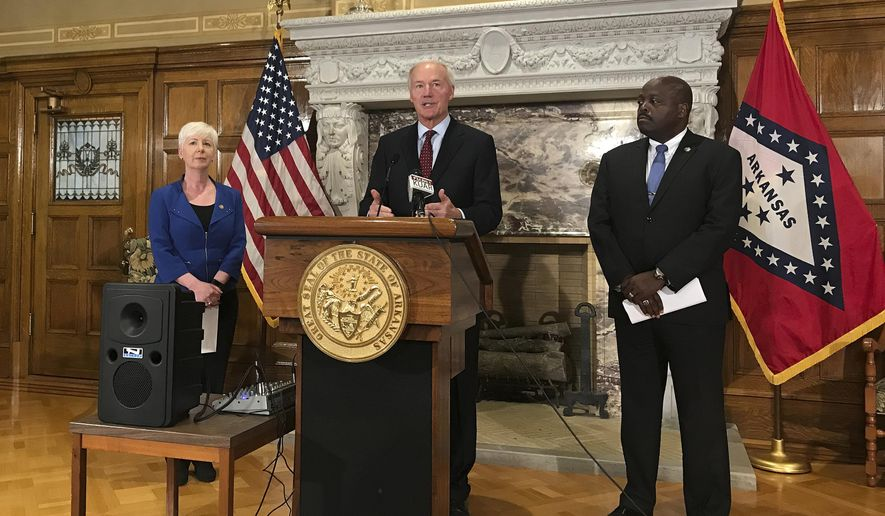FILE - In this Sept. 12, 2018, file photo, Arkansas Gov. Asa Hutchinson, center, talks at a news conference at the State Capitol in Little Rock, Ark., about the state's work requirement for its expanded Medicaid program. Federal judge James Boasberg is blocking Medicaid work requirements in Arkansas and Kentucky, dealing a blow to the Trump administration's efforts to push the poor toward self-sufficiency. Boasberg issued two decisions Wednesday, March 27, finding that Medicaid work requirements for low-income people in Arkansas and Kentucky pose numerous obstacles to getting health care that haven't been adequately addressed by federal and state officials. (AP Photo/Andrew DeMillo, File)
