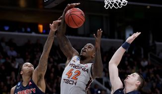 Virginia Tech guard Ty Outlaw, middle, vies for a rebound with Liberty guard Caleb Homesley, left, and Scottie James during the second half of a second-round game in the NCAA men's college basketball tournament Sunday, March 24, 2019, in San Jose, Calif. (AP Photo/Ben Margot) **FILE**