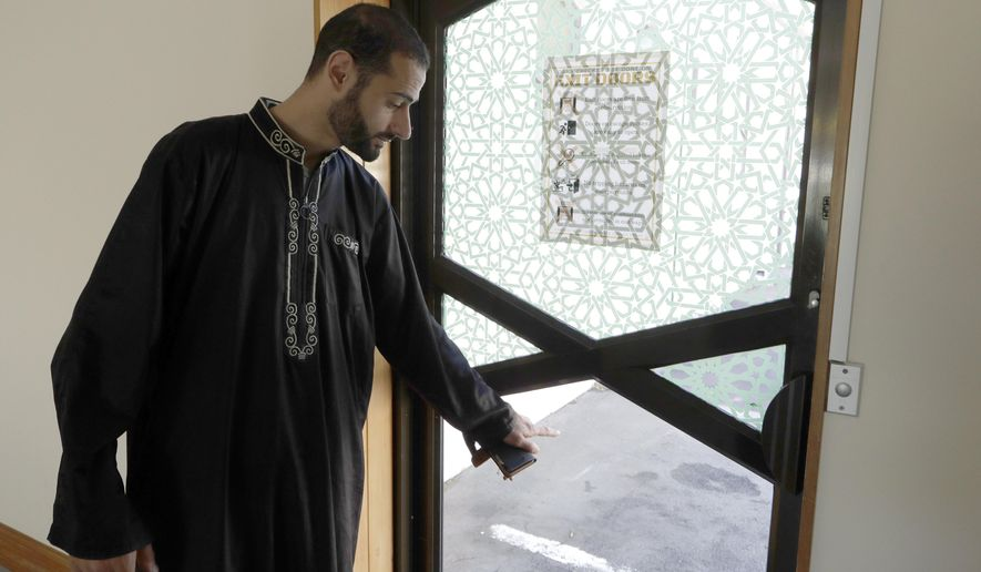 In this March 27, 2019, photo, Al Noor mosque volunteer Khaled Alnobani gestures as he explains his escape through a glass door panel when a gunman burst into the mosque on March 15 in Christchurch, New Zealand. Alnobani says he thinks as many as 17 people may have died trying to get out through the door.(AP Photo/Mark Baker)