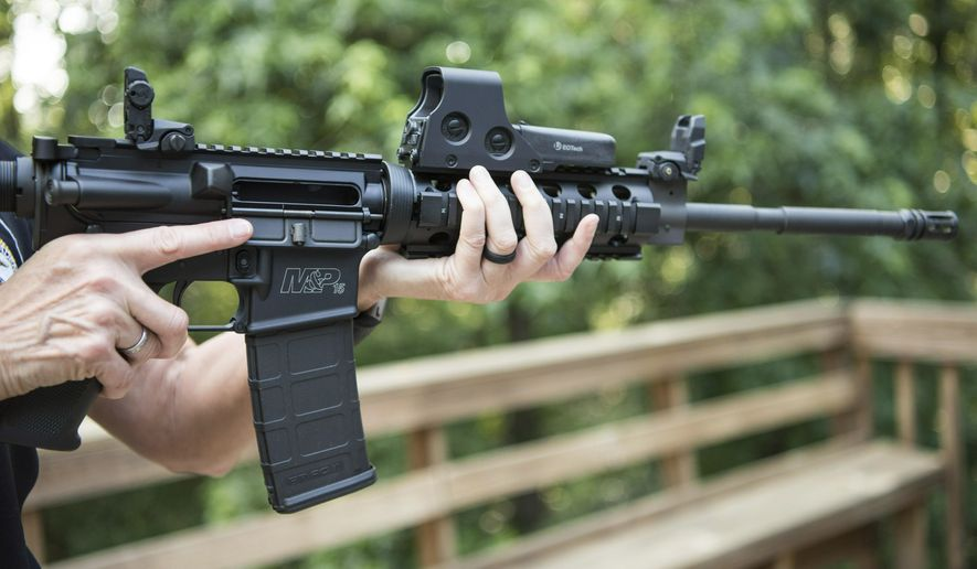 FILE - In this June 24, 2016 file photo, an AR-15 is held in Auburn, Ga.  The Pittsburgh City Council gave initial approval Wednesday, March 27, 2019,  to gun-control legislation introduced in wake of the 2018 synagogue massacre, an effort certain to be challenged in court by Second Amendment advocates who point out that state law doesn't allow municipalities to regulate firearms. The legislation would place restrictions on military-style assault weapons like the AR-15 rifle that authorities say was used in the Oct. 27 rampage at Tree of Life Synagogue that killed 11 and wounded seven.(AP Photo/Lisa Marie Pane, File)