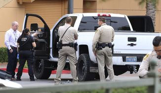 Las Vegas police surround a white pickup truck as they investigate after a pursuit related to the officer-involved shooting that ended at the Golden Nugget hotel-casino on Wednesday, March. 27, 2019, in Las Vegas. Authorities say a Las Vegas police officer shot a jail prisoner who escaped in shackles in a stolen pickup truck after a medical clinic visit and led officers on a wreck-filled chase before running out of gas near downtown casinos. (Bizuayehu Tesfaye/Las Vegas Review-Journal via AP)
