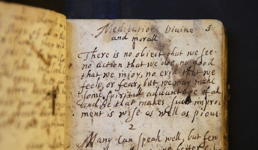 """In this Wednesday, March 20, 2019, photo provided by the Board of Trustees of Stevens Memorial Library, a handwritten manuscript called """"Meditations Divine and Moral,"""" by 17th century poet Anne Bradstreet, rests on a table at the Houghton Library on the campus of Harvard University, in Cambridge, Mass. Bradstreet was the North American continent's first published poet. Her actual burial place is not known. (Courtesy of Board of Trustees of Stevens Memorial Library via AP)"""