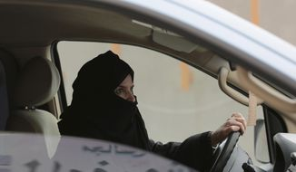 FILE - In this March 29, 2014 file photo, Aziza al-Yousef drives a car on a highway in Riyadh, Saudi Arabia, as part of a campaign to defy Saudi Arabia's then ban on women driving. Saudi women's rights activists, including  al-Yousef, are expected to appear before a judge Wednesday, March 27, 2019, on charges that include speaking to foreign journalists. Several people with knowledge of the cases say the charges for the nearly dozen women relate to their efforts to promote women's rights and sharing information with accredited foreign reporters, diplomats and human rights groups.  (AP Photo/Hasan Jamali, File)