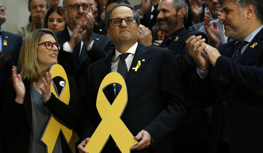 FILE - In this Monday, May 14, 2018 file photo, newly appointed Catalan president Quim Torra, center, holds a yellow ribbon in support of Catalonian politicians who have been jailed on charges of sedition, at the end of a parliamentary vote session in Barcelona, Spain. Prosecutors in Spain said in a statement Wednesday March 27, 2019, they are bringing charges of disobedience against Catalan regional president Quim Torra after he allegedly failed to comply with orders from the country's electoral board. (AP Photo/Manu Fernandez, File)