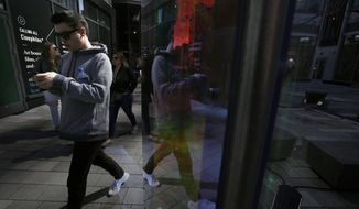In this Sunday, March 24, 2019 photo people walk on a pedestrian walkway, in Boston's Seaport district. Apple's latest move into streaming video illustrates an escalating trend: Tech's biggest companies, faced with limits to their growth, are encroaching on each other's turf. (AP Photo/Steven Senne)