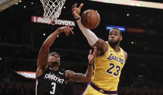 Los Angeles Lakers' LeBron James, right, grabs a rebound against Washington Wizards' Bradley Beal during the first half of an NBA basketball game, Tuesday, March 26, 2019, in Los Angeles. (AP Photo/Jae C. Hong) ** FILE **