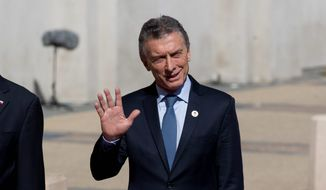 Argentina's President Mauricio Macri waves to journalists upon his arrival to La Moneda, presidential palace in Santiago, Chile, Friday, March 22, 2019. South American heads of state are meeting in Santiago to discuss the development of a new regional political bloc called Prosur, the idea being to replace the Unasur, the current body that many describe as defunct. (AP Photo/Esteban Felix)