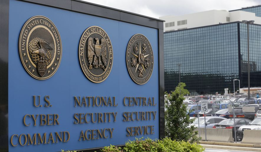 In this June 6, 2013, file photo, vehicles are parked near a sign outside the National Security Agency campus in Fort Meade, Md. (AP Photo/Patrick Semansky, File) ** FILE **