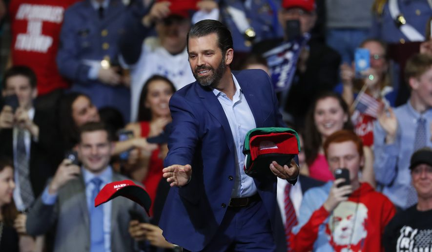 Donald Trump Jr. tosses hats to the audience during a rally in Grand Rapids, Mich., Thursday, March 28, 2019. (AP Photo/Paul Sancya)