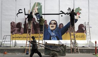 In this March 8, 2019, file photo, an independent Afghan artist draws graffiti on a barrier wall of the Ministry of Women's Affairs to mark International Women's Day, in Kabul, Afghanistan. (AP Photo/Rahmat Gul, File)