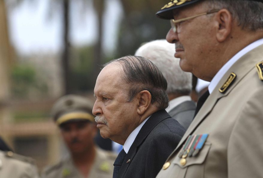 In this picture taken on June 27, 2012, Algerian President Abdelaziz Bouteflika, left, and his Army chief of staff, Gen. Ahmed Gaid Salah, review an honor guard before attending a military parade, in Cherchell near Algiers, Algeria. Algeria's powerful army chief, Ahmed Gaid Salah, insisted Wednesday that the military won't get mixed up in politics, a day after he said a constitutional process should be set in motion to declare ailing President Abdelaziz Bouteflika unfit for office. (AP Photo/Anis Belghoul)