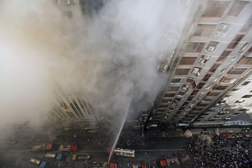 Firefighters work to douse a fire in a multi-storied office building in Dhaka, Bangladesh, Thursday, March 28, 2019. A fire in a high-rise office building in Bangladesh's capital on Thursday killed seven people and injured dozens more, police said. (AP Photo/Mahmud Hossain Opu )