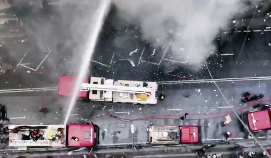In this image made from video, firetrucks hose down a building on fire in the Banani area of Dhaka, Bangladesh, Thursday, March 28, 2019. An official in the Fire Department control room says the fire had broken out in an office building in Bangladesh's capital, and some people are feared trapped inside. (AP Photo)